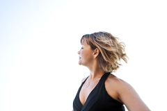 Woman Health Movement. Portrait of a vital adult woman in free movement against a natural white sky royalty free stock photography