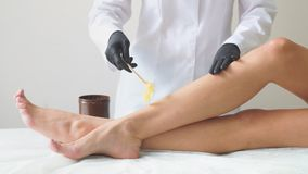 Woman health care leg depilation professional work close-up. Hard warm wax on female body parts done in the studio.