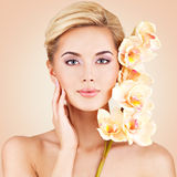 Woman with health skin and flowers at face. Royalty Free Stock Image