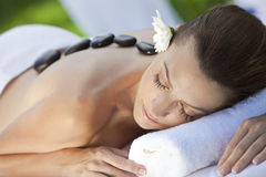 Woman At Health Spa Having Hot Stone Massage. A woman relaxing at a health spa while having a hot stone treatment or massage Royalty Free Stock Image