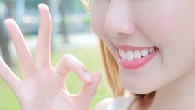 Woman with health teeth. Close up of beauty woman smile with health teeth and show OK stock photography