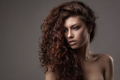 Woman with healthy brown curly hair. Studio shot of woman with healthy brown curly hair isolated over grey background stock image
