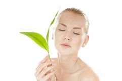 Woman with a healthy  complexion holding green leaf. Royalty Free Stock Photography