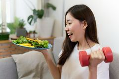 Young Asian girl holding salad and red dumbbell is sitting on sofa with smile face. stock photography