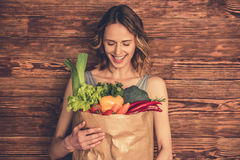 Woman with healthy food. Beautiful young woman in sportswear is holding a shopping bag full of healthy food, looking at camera and smiling, on wooden background Royalty Free Stock Photo