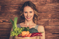 Woman with healthy food. Beautiful young woman in sportswear is holding a shopping bag full of healthy food, looking at camera and smiling, on wooden background Stock Photos