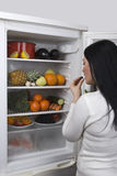 Woman with healthy food in fridge. A young woman eating a grape berry from a full fridge with fresh fruits and vegetables.Check out also stock photography