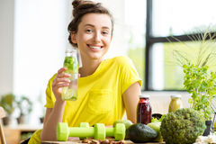 Woman with healthy food indoors. Portrait of a young sports woman in yellow t-shirt sitting indoors with healthy food and dumbbells on the table royalty free stock photos
