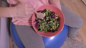 Woman with healthy food after workout. Ball in room stock video footage