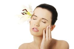 Woman with healthy skin and lily flower Stock Photos