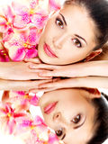 Woman with healthy skin and pink flowers reflections in a mirro Stock Photography