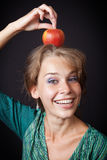 Woman with healthy teeth and apple on head. Happy woman with healthy teeth and apple on head Stock Photo