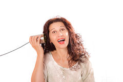 Woman hearing through tin phones. Portrait of a cute middle aged woman hearing through tin can phones isolated over a white background Royalty Free Stock Images