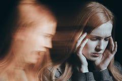 Woman hearing voices. Ill woman hearing voices in her head stock photo