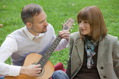 Woman hears love song. Man playing acoustic guitar by romantic picnic outdoors Royalty Free Stock Photos
