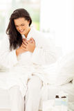 Woman heart attack. Young woman in pajamas having heart attack Royalty Free Stock Photography