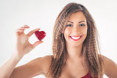 Woman With Heart. Beautiful smiling girl holding a red heart. Selective focus. Focus on the girl Royalty Free Stock Photo