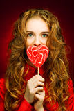 Woman with heart caramel over red background Royalty Free Stock Photography