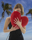 Woman with heart pillow Royalty Free Stock Photography