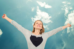 Woman with heart raising arms above head and sky. Woman with the symbol of heart on her T-shirt raising arms above her head and the sky as a background Royalty Free Stock Photo