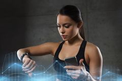 Woman with heart-rate watch and smartphone in gym Royalty Free Stock Photo