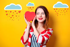 Woman with heart shape box on yellow background Stock Images