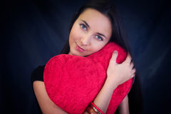Woman with heart shaped cushion Stock Photography
