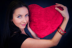 Woman with heart shaped cushion Stock Images