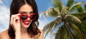 Woman in heart shaped shades over palm tree. Valentines day, beauty and people concept - close up of happy smiling young woman with red lipstick and heart shaped Royalty Free Stock Photos