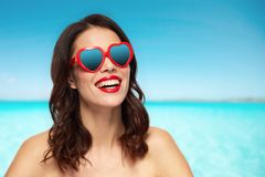 Woman with heart shaped shades over sea and sky. Valentines day, summer vacation, travel and tourism concept - happy smiling young woman with red lipstick and Royalty Free Stock Photography