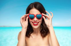 Woman with heart shaped shades over sea and sky. Valentines day, summer vacation, travel and tourism concept - happy smiling young woman with red lipstick and Royalty Free Stock Photo