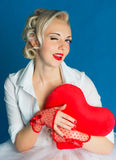 Woman heart Valentine's Day. Woman wink and holding a big heart on Valentine's Day Royalty Free Stock Photography