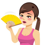 Woman Heated. Young beautiful woman heated fanning with yellow fan Stock Photography