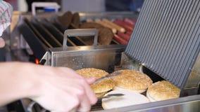 Woman heats fresh buns to prepare hamburger in fastfood cafe