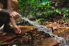 Woman heaving fun with hosepipe splashing water. In the jungle with jungle in the background Royalty Free Stock Photography