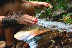 Woman heaving fun with hosepipe splashing water. In the jungle with jungle in the background Royalty Free Stock Photo