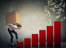 Woman with heavy box on her back climbing up financial success ladder Stock Images