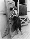 Woman with heavy door Stock Image