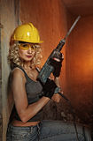 Woman with heavy perforator. Beautiful blond woman with heavy perforator in her hands Royalty Free Stock Photo
