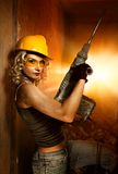 Woman with heavy perforator. Beautiful blond woman with heavy perforator in her hands Royalty Free Stock Images