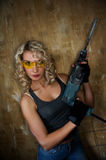 Woman with heavy perforator. Beautiful blond woman with heavy perforator in her hands Stock Image