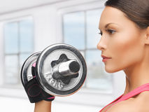 Woman with heavy steel dumbbell Royalty Free Stock Photography