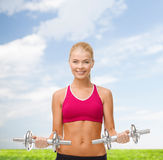 Woman with heavy steel dumbbells Royalty Free Stock Images