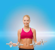 Woman with heavy steel dumbbells Royalty Free Stock Photography