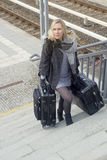 Woman with heavy suitcases walking up stairs at train station Stock Photo