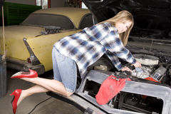 Woman in heels car. A woman wearing her red heels while she is working on her car engine Royalty Free Stock Photo