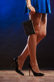 Woman in heels holds handbag, disco club. Celebration disco and evening fashion concept - woman in blue dress holding handbag bag, dancing in the club, part of Royalty Free Stock Photos