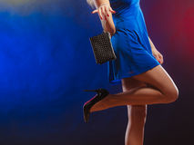 Woman in heels holds handbag, disco club. Celebration disco and evening fashion concept - woman in blue dress holding handbag bag, dancing in the club, part of Royalty Free Stock Image