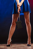 Woman in heels holds handbag, disco club. Celebration disco and evening fashion concept - woman in blue dress holding handbag bag, dancing in the club, part of Stock Photo