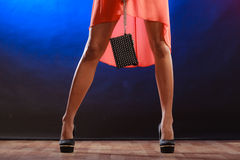 Woman in heels holds handbag, disco club. Celebration disco and evening fashion concept - woman in orange dress holding handbag bag, dancing in the club, part of Royalty Free Stock Image